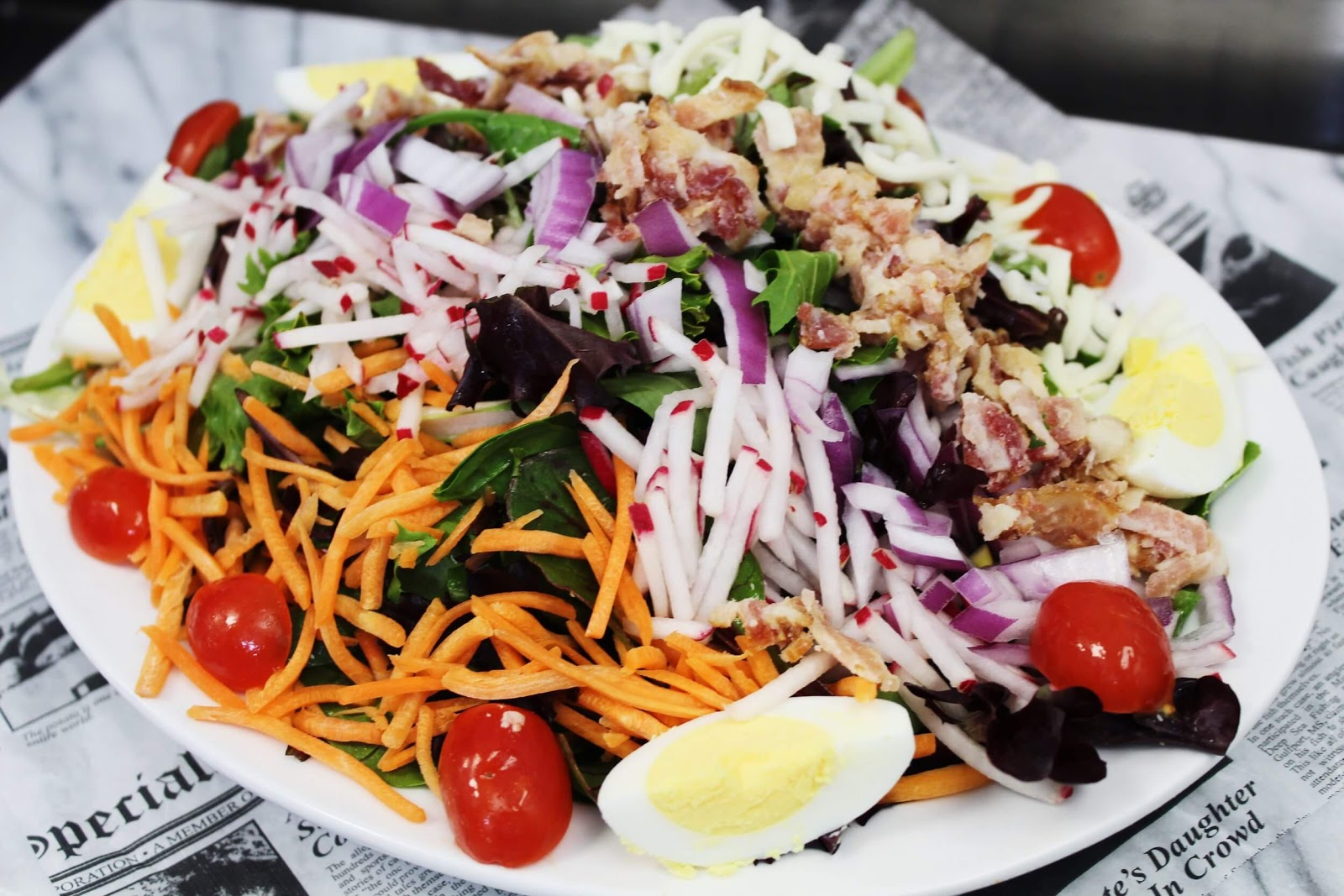 Salad with red onions, cherry tomatoes, carrots, and boiled eggs