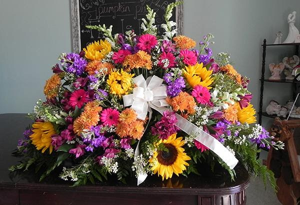 Floral arrangement of sunflowers, pink flowers, and purple flowers