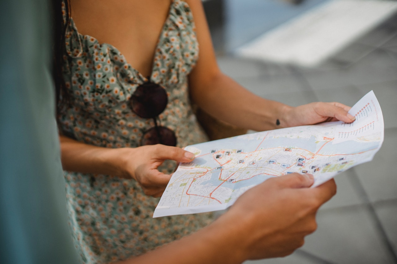 Two people hold a map of a city
