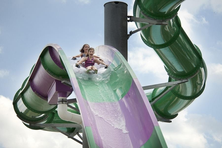 Two children smiling as they slide down a large purple and green water slide