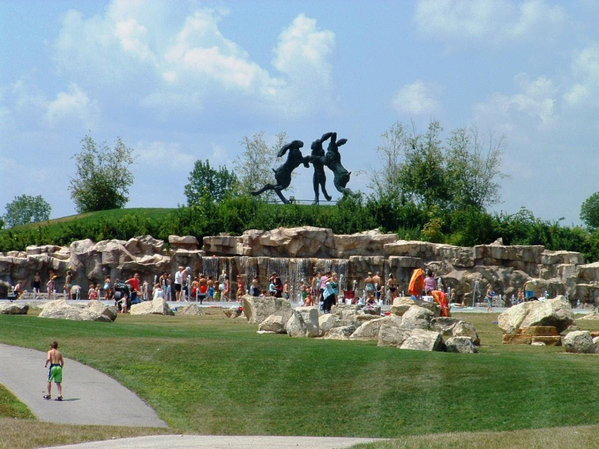 A wide view of people standing in spray water fountains with rocks, grass, trees, and a statue of three bunnies behind them