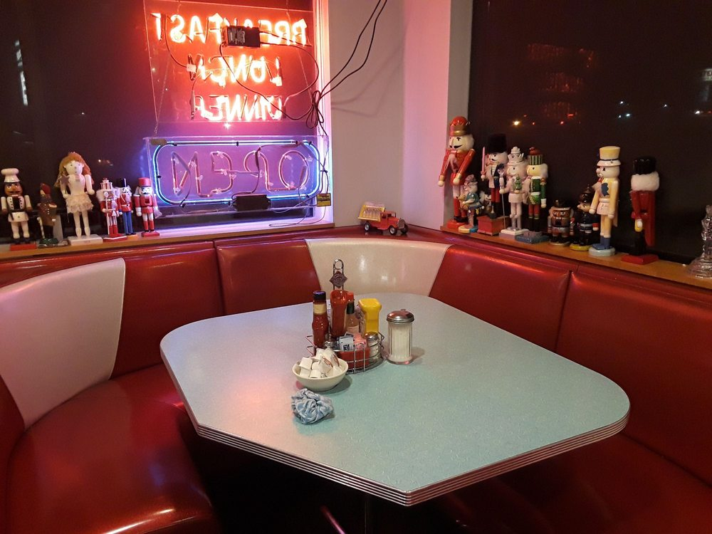 Vintage red diner booth with condiments on the table and nutcracker toys shelved around the booth