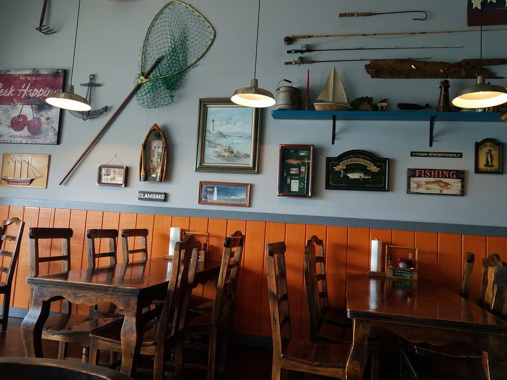 Interior of seafood restaurant with fish nets, framed paintings, and other fishermen decor on the walls