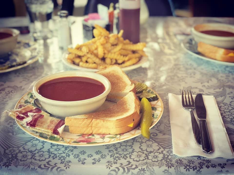 Tomato soup and grilled cheese sandwich on a plate with french fries on a plate behind it