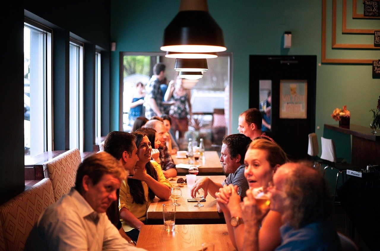 Several tables of people talking and eating in a restaurant