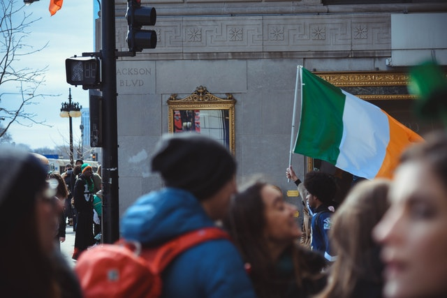 Crowd of people with Irish flag in background