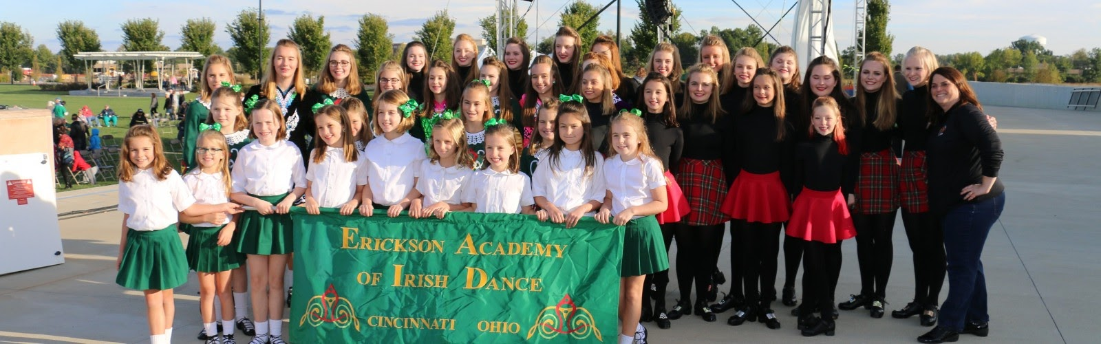 Young dancers from the academy pose with their flag