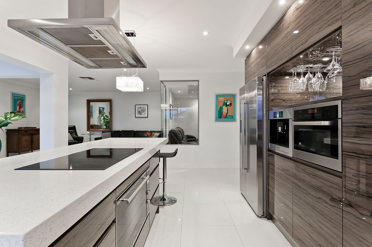 A large open-aired kitchen with white countertops and a sleek-chrome design.