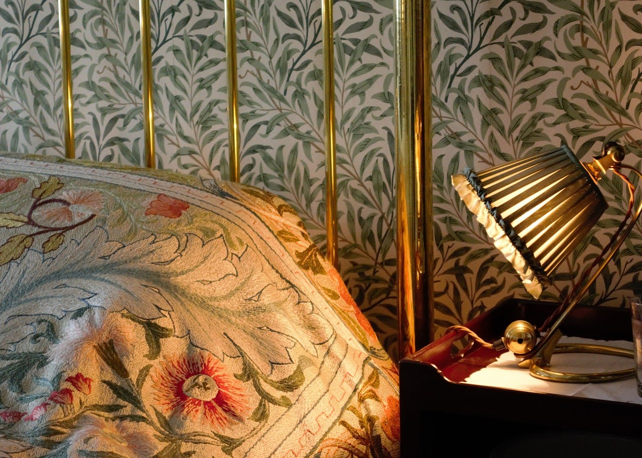 Closeup on a brass headboard and side table with a lamp. The wallpaper behind the bed is plant and leaf themed.