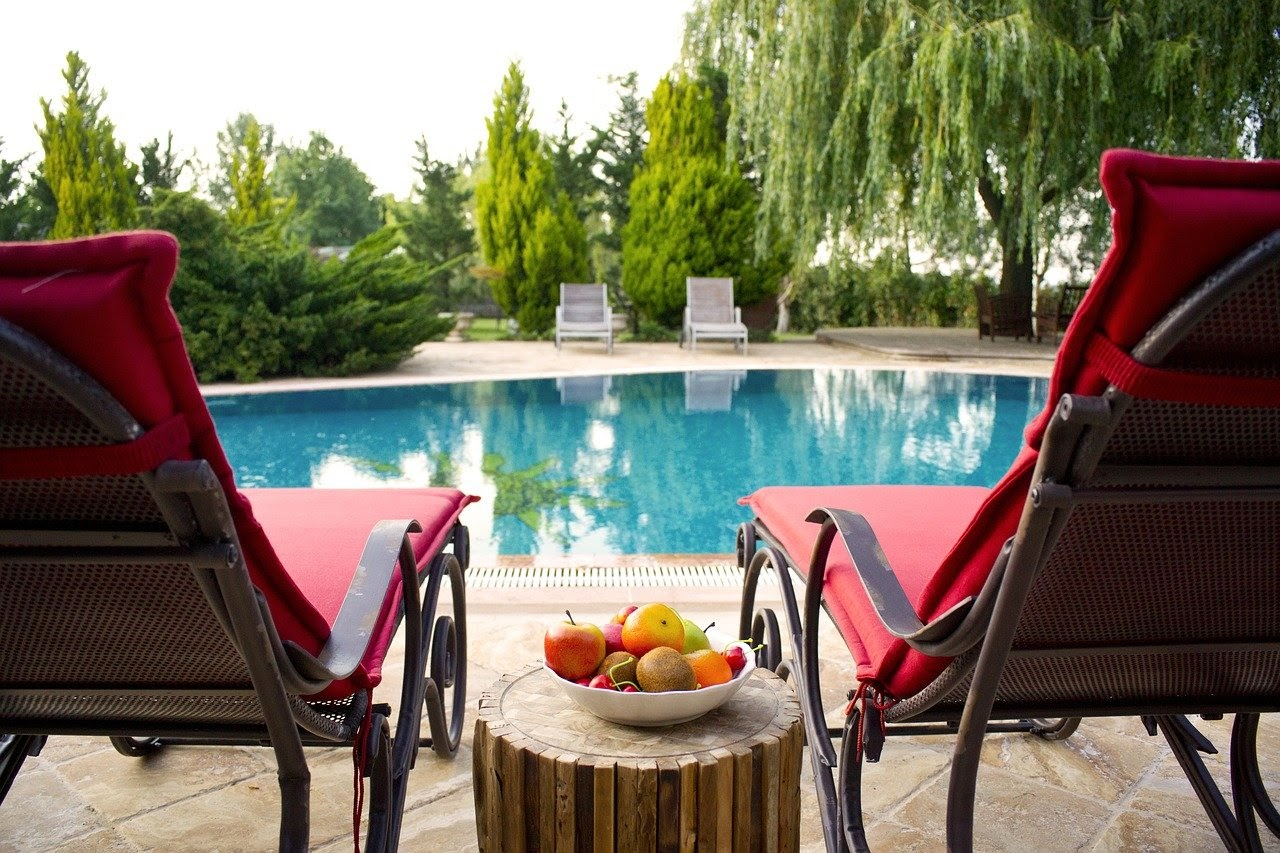 Two red lawn chairs by a poolside. In between them there is an end table with a bowl of fruit on top.