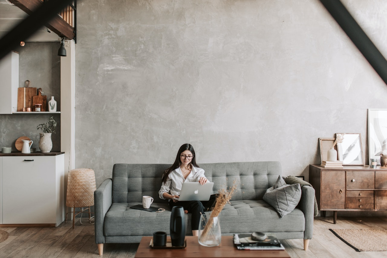 A woman in a white shirt sits on her couch looking at her laptop in a stylishly decorated room.