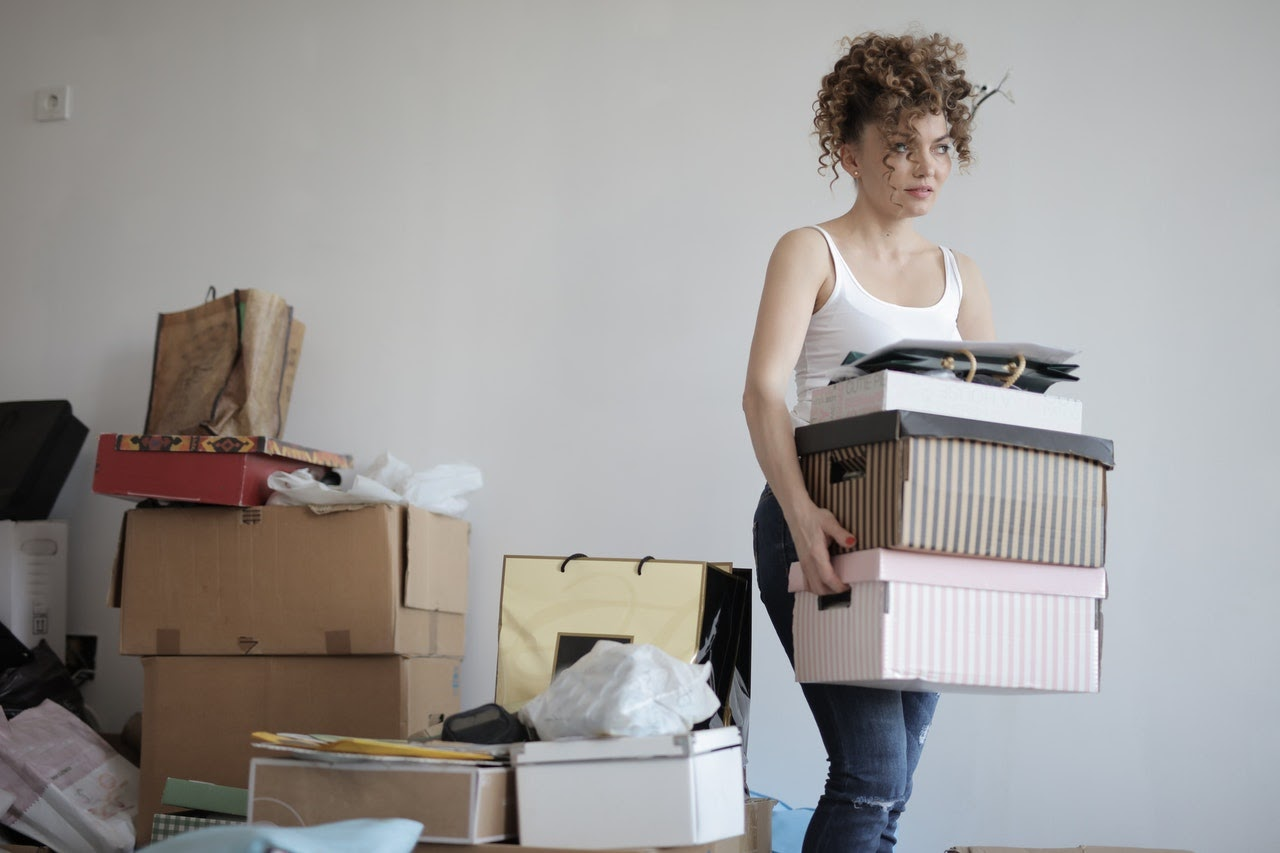 A woman with curly hair has a couple of colorful boxes in her hands. Behind her there is a pile of more stuff to move.
