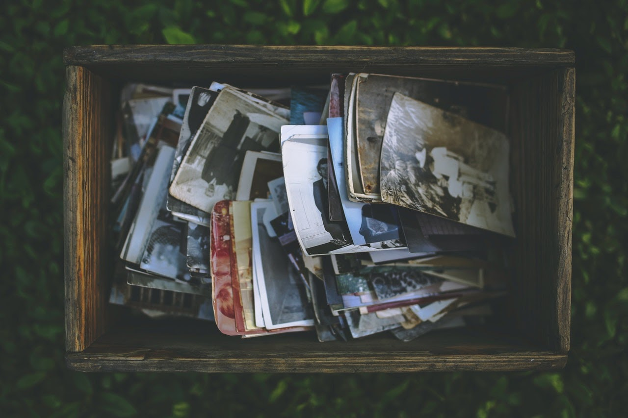 A wooden box full on antique and worn looking photos sits on the grass outside.