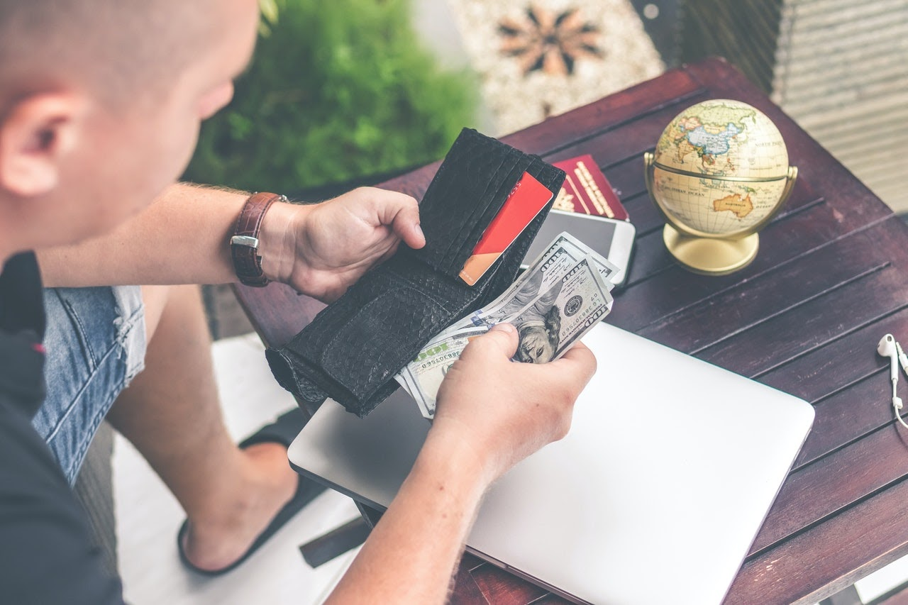A man looks at the contents of his wallet over an wooden end table with a small globe on it. He's holding three hundred dollar bills in his hand.