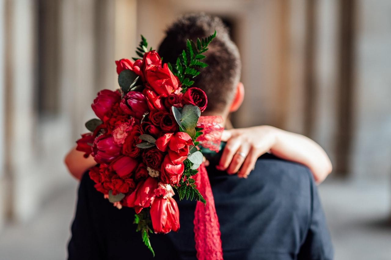 A couple is hugging. The woman has her hands around the man's shoulders, and in her hands is a bouquet of red flowers.