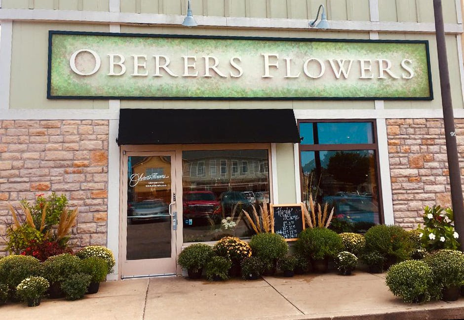 A picture of the Oberer's Flowers storefront. The sign is green and there are shrubs out front.