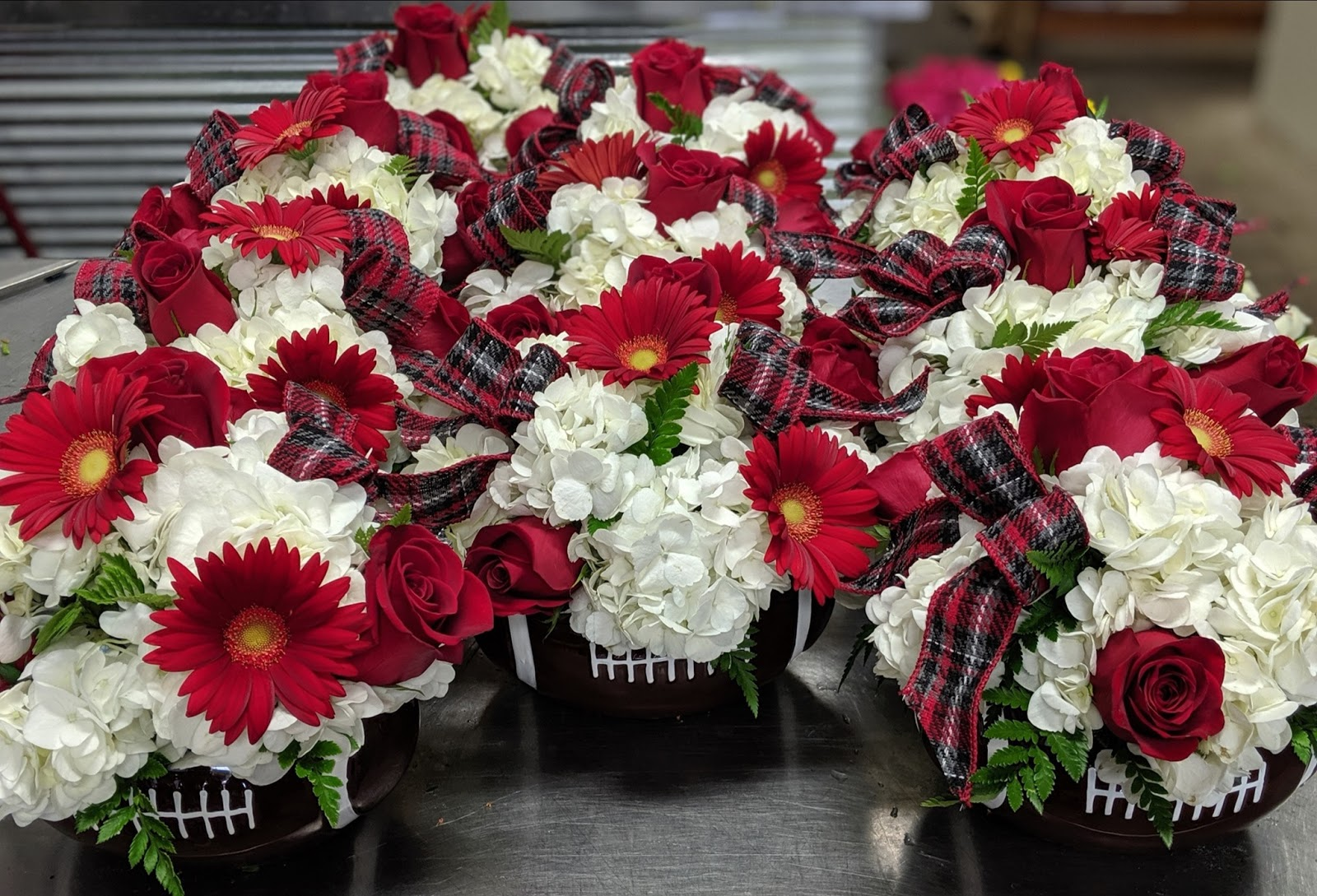 Customized red and white bouquets of flowers potted in small football pots, in the spirit of the Ohio State Buckeye's.