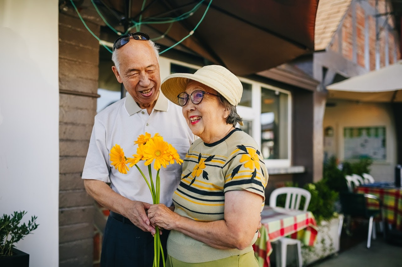 An image of an older asian couple. They're both smiling and the woman is holding a large bouquet of yellow gerber daises in her hand.