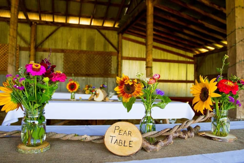 "A shot of a table arranged with flower bouquets. There are sunflowers and small purple flowers in them. And a sign that says ""Pear Table""."