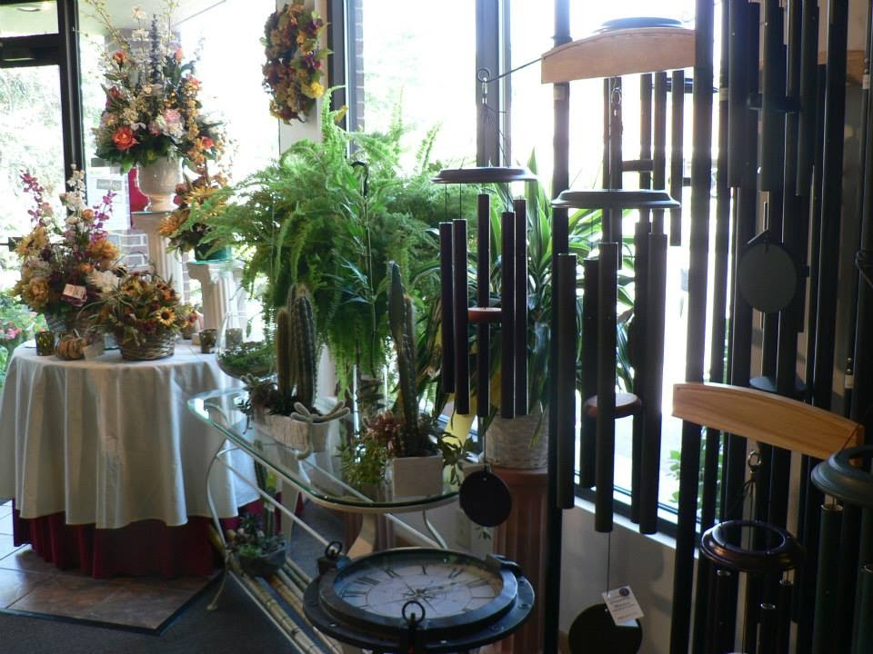 An inside shot of Ree's Flowers and Gifts. There are tables full of flowers and plants and hanging wind chimes.