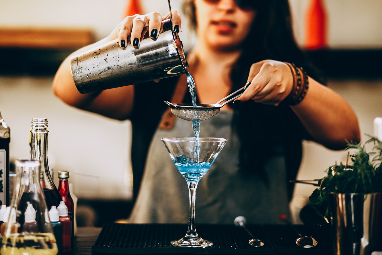 A bartender stands making a blue cocktail. In her hands are a spoon and a drink shaker.