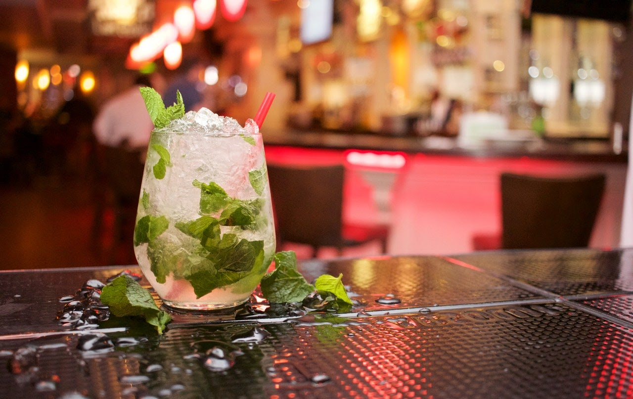 A closeup of a mixed cocktail sitting on a bar top. It's full of ice and mint leaves.