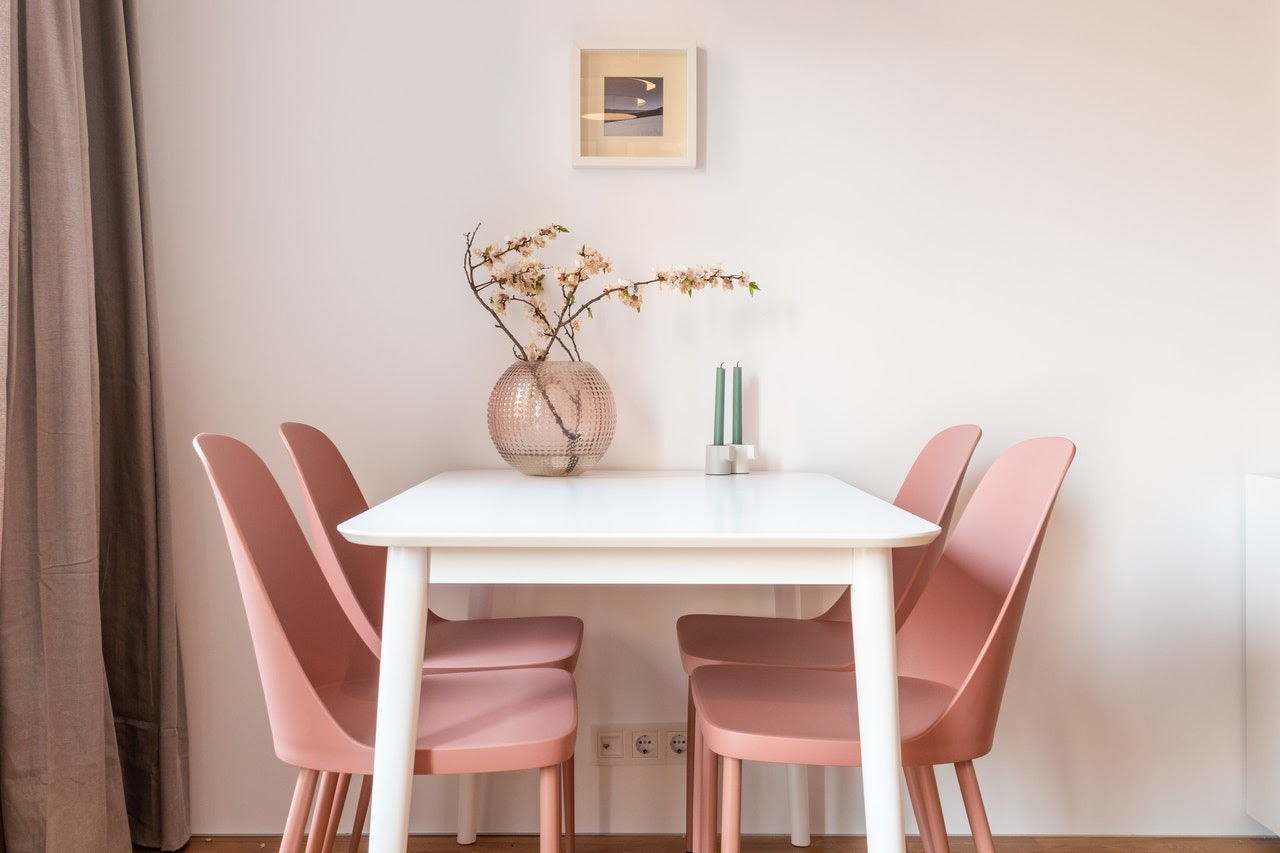 A white table in the center with four pin chairs. On the table is a circular pink base with flowers in it. Also two green candles and a painting on the wall.