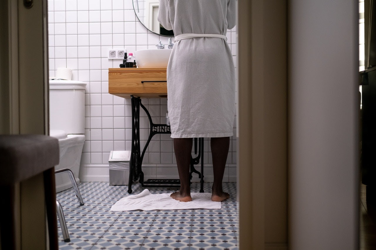 A look into a bathroom from the doorway. A man stands at the sink washing his hands and a toilet is visible on the left.
