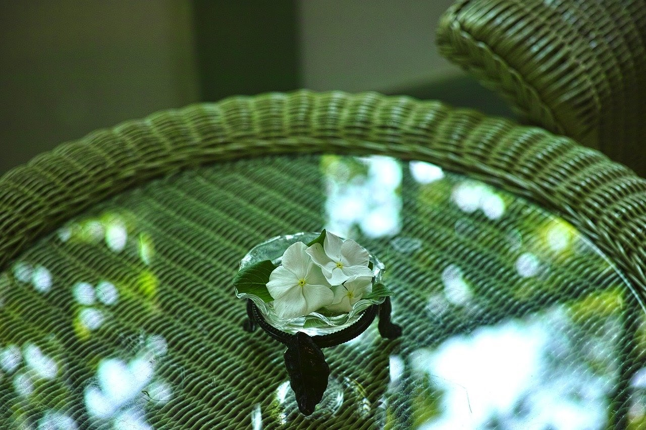 A close-up of a glass and rattan table on the top is an ashtray with flower petals inside.