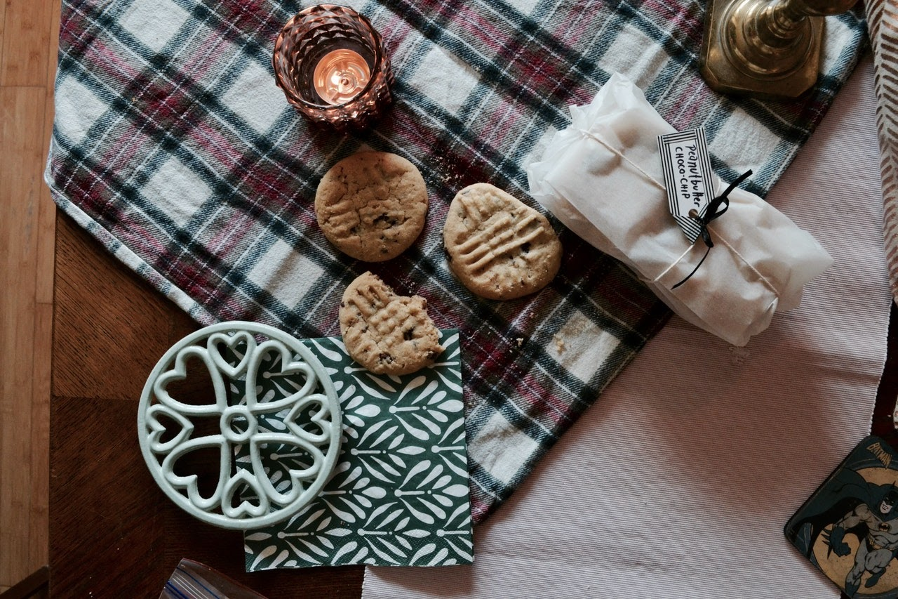 A top view of a plaid blanket on a table. On the blanket are some cookies, a candle, and a green napkin.