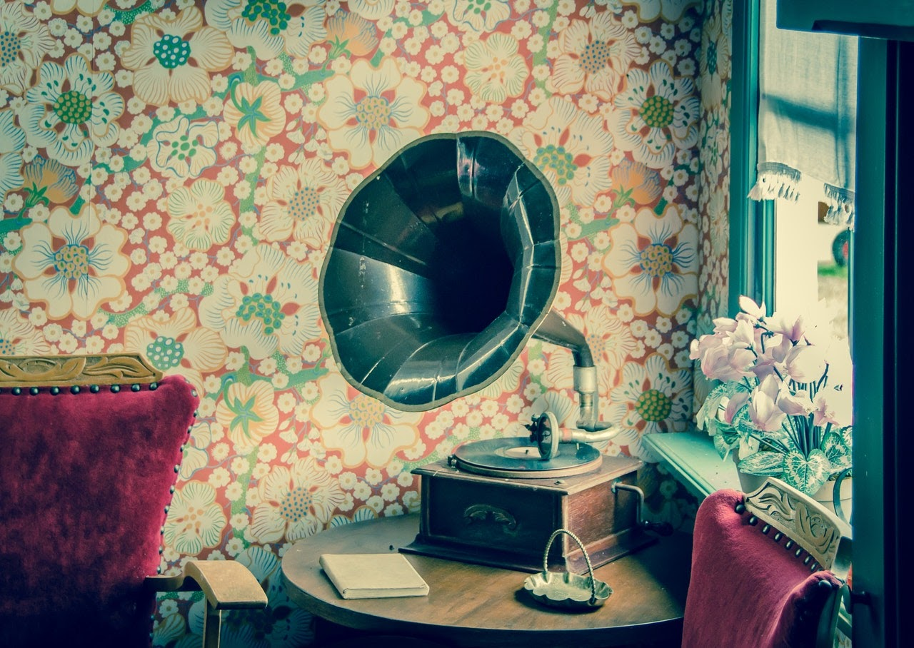 An old record player sits on a table. Behind it the wallpaper is bright and floral. Colored in red and white.