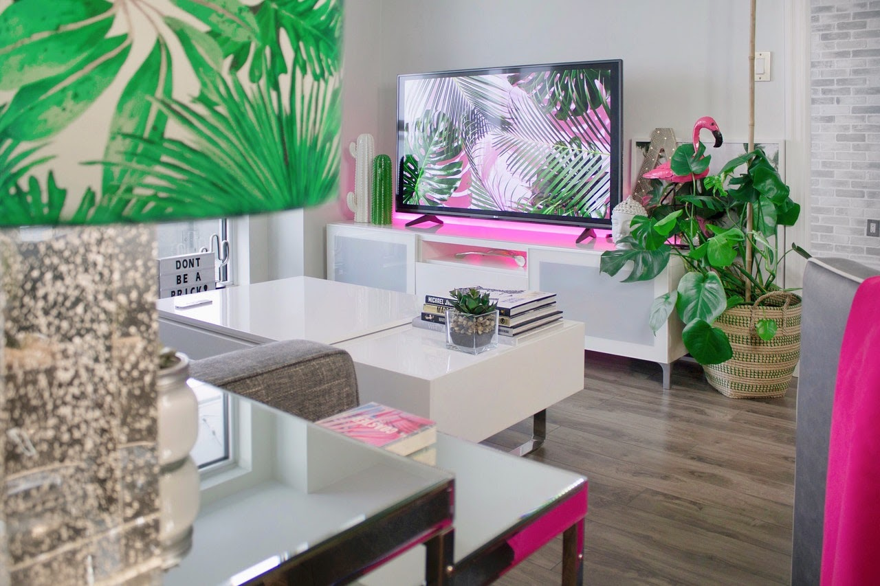 A modern looking living room with a plant theme lampshade. White sleek tables, and accents of pink all over. A pink flamingo, a pink light under the tv, and pink books.