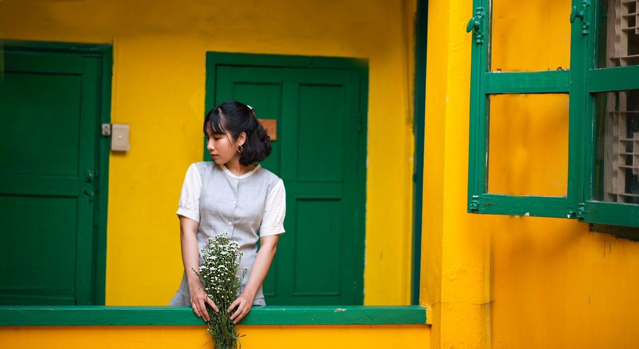 A woman stands on an outside balcony with her hands over the rails. The walls are a bright yellow and the windows have green trim. In her hands is a bouquet of white flowers.
