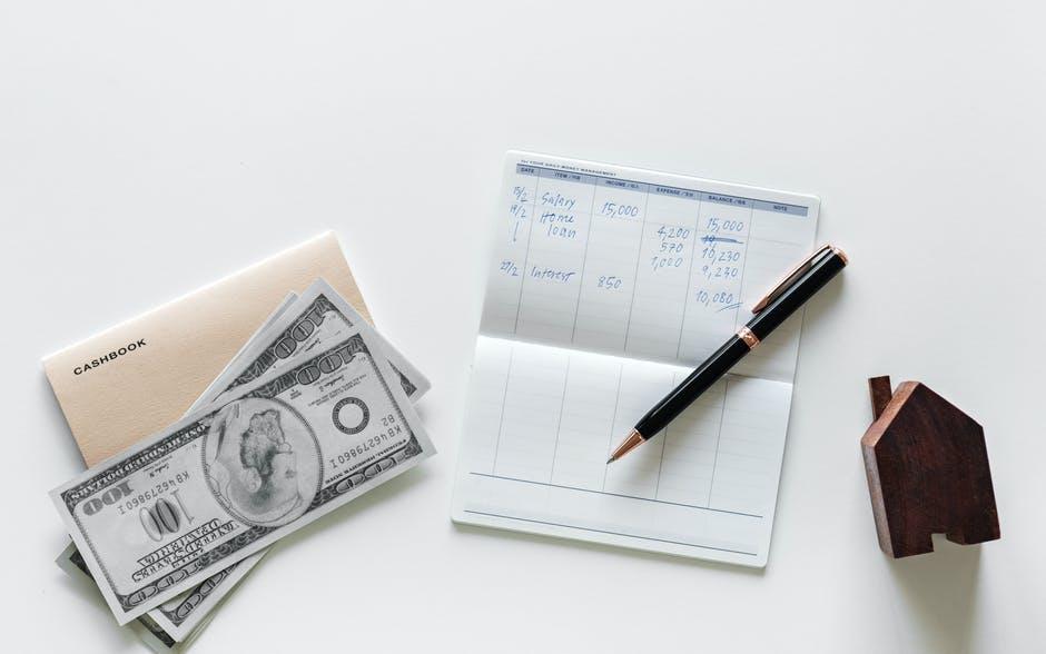 ballpoint pen on top of white paper beside 100 US dollar bills