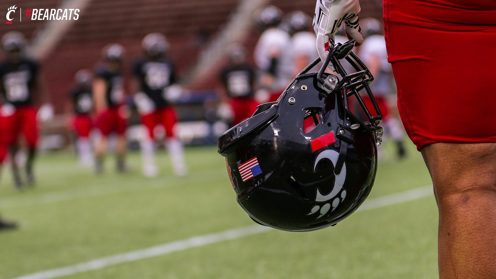 a player holding the Cincinnati Bearcats football helmet with other players in the background
