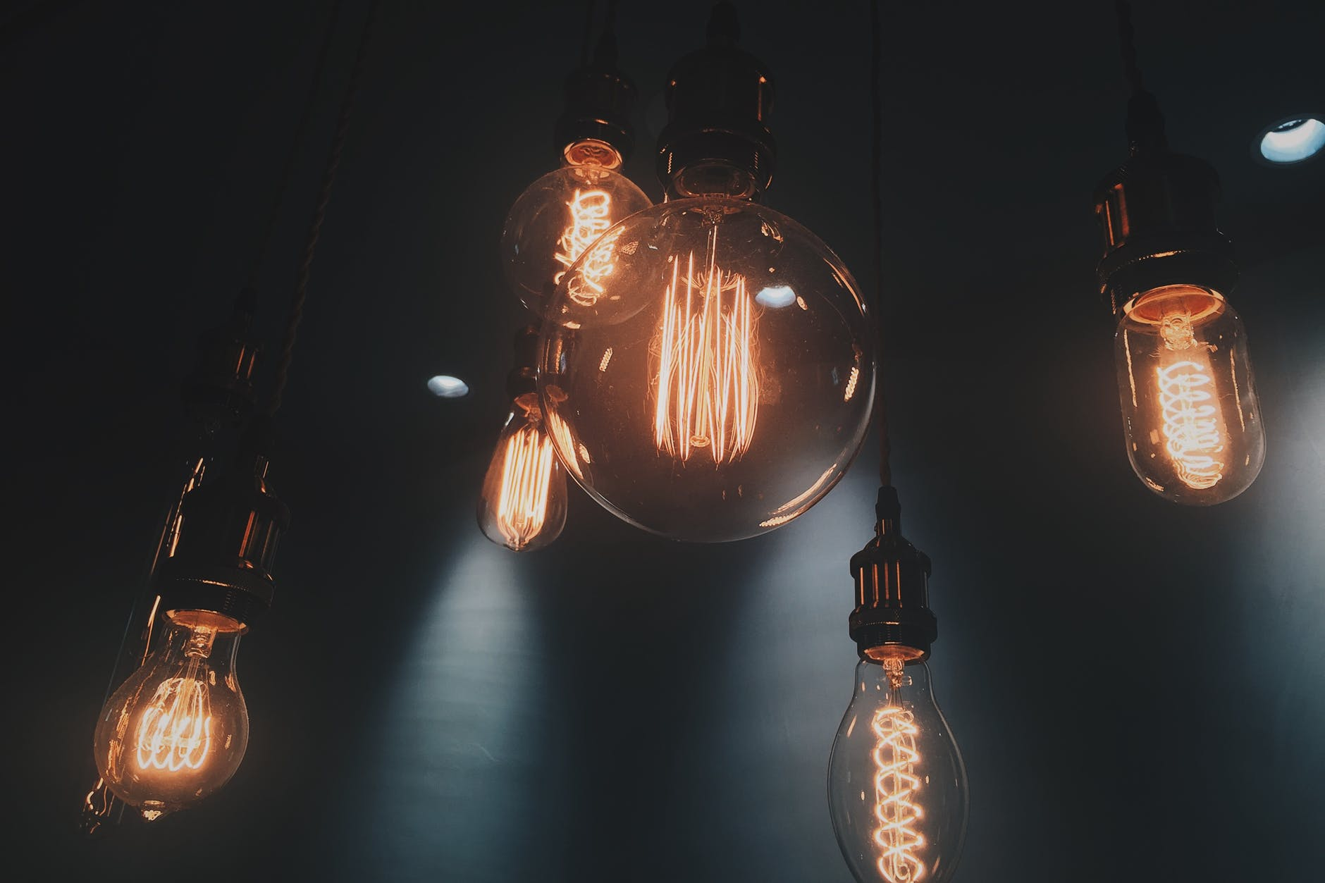 several light bulbs hanging from ceiling in dark room