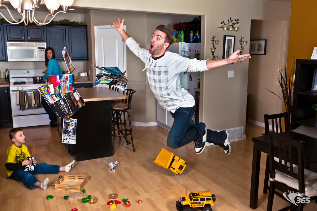 man tripping over toys scattered over kitchen floor