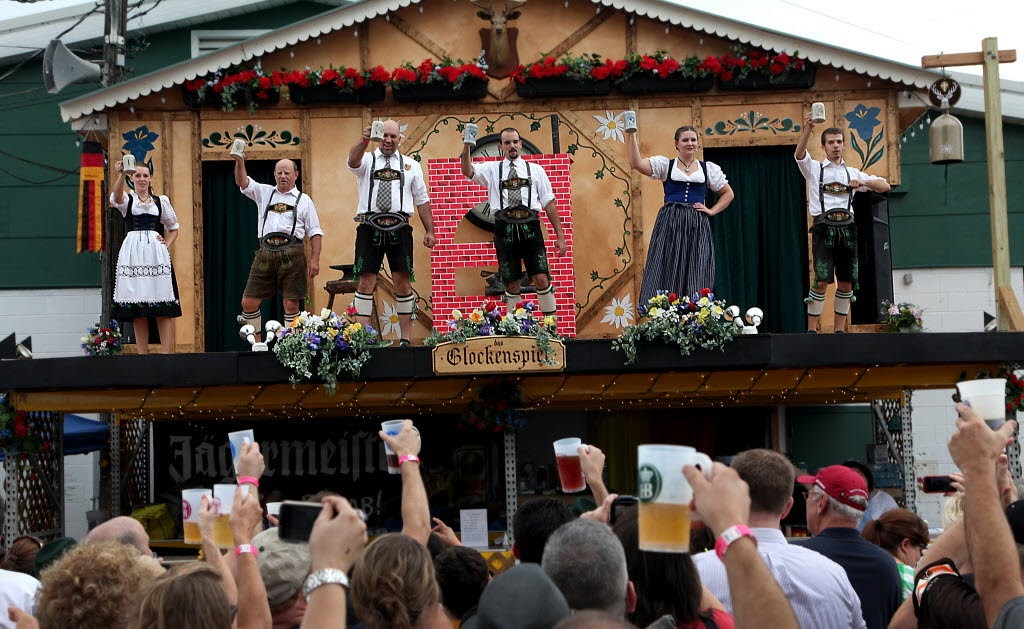 people dressed in old folk clothing holding up beer pitchers on stage