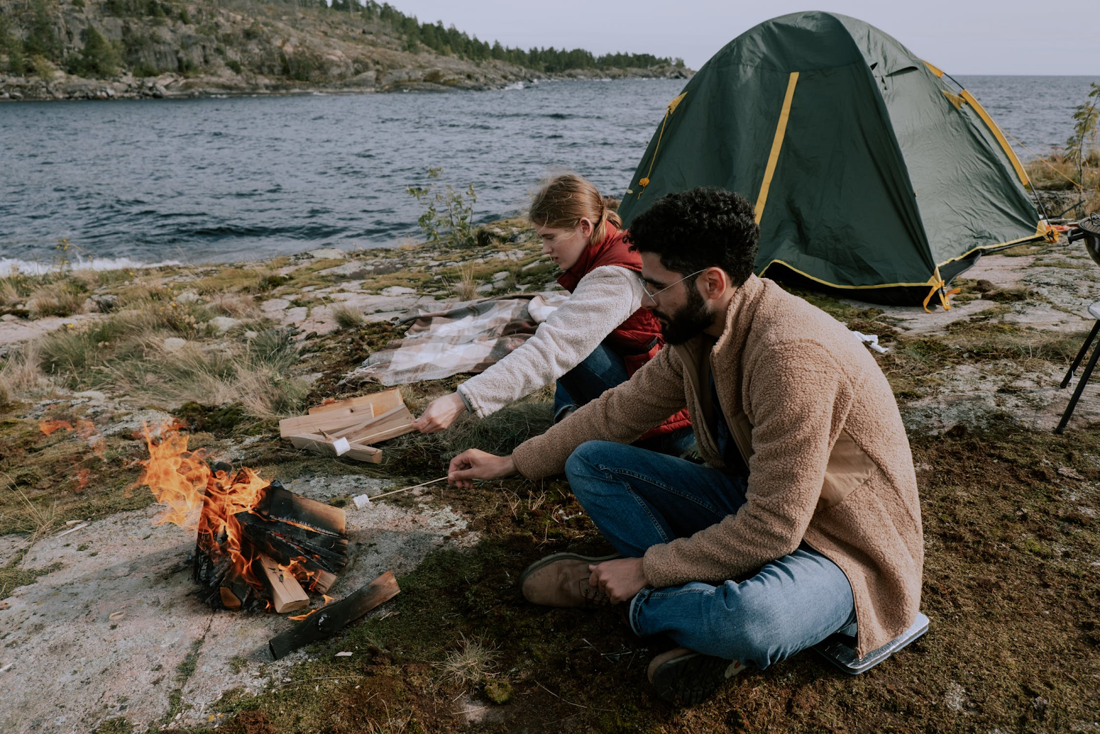 An image showing two people roasting marshmallows, a common activity during camping trips.