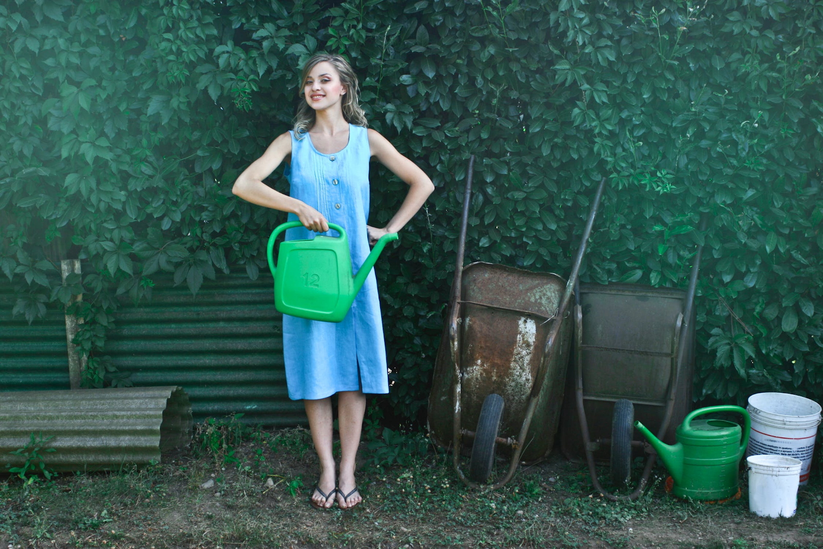 smiling woman in a blue dress holding green watering can in a garden