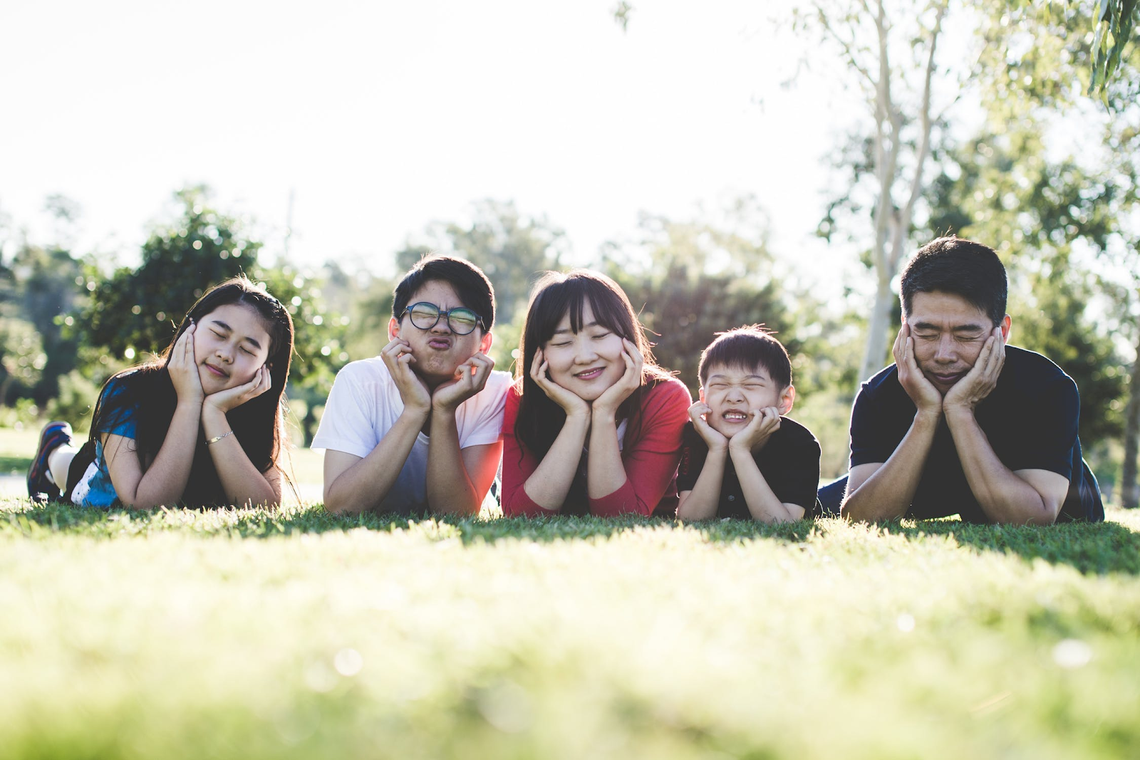 family laying in a field making funny faces