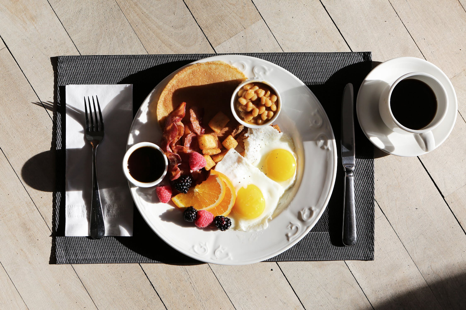 overhead view of a plate with eggs, toast, fruit, and beans and a cup of coffee