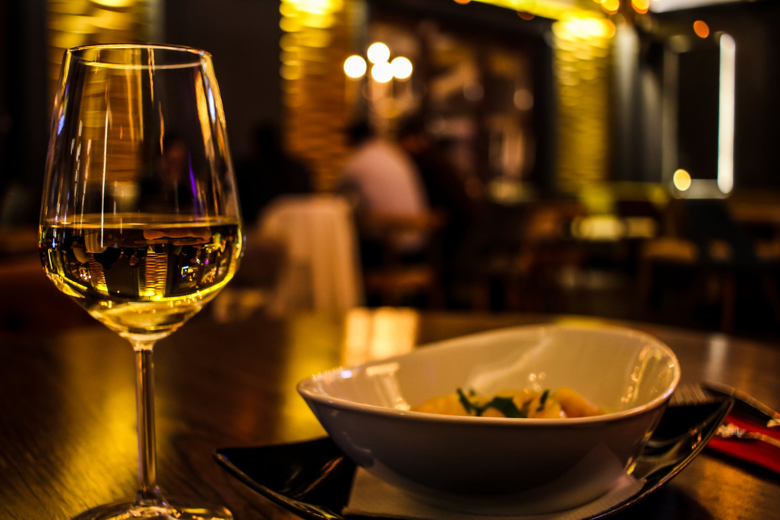 dish and a glass of wine in a dimly lit restaurant