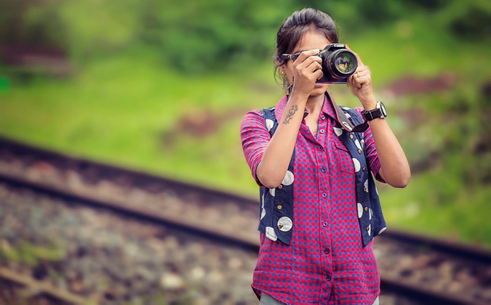 woman in red plaid shirt taking a photo in front of a railroad