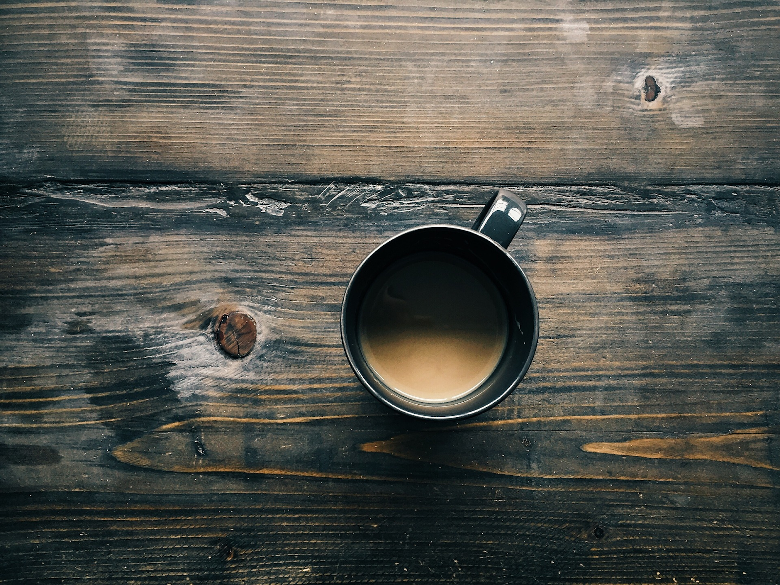 overhead view of coffee mug on wooden table