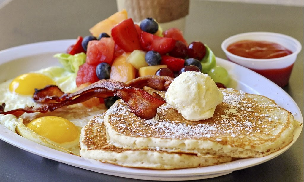 pancakes, bacon, sunny-side-up eggs, and fruit on a plate