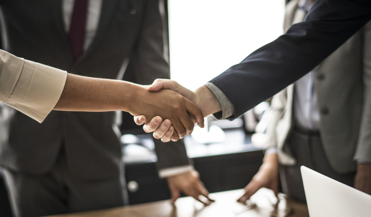 people in suits shaking hands