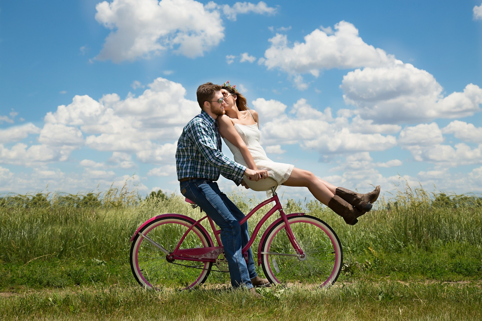 young couple riding a red bicycle in a field