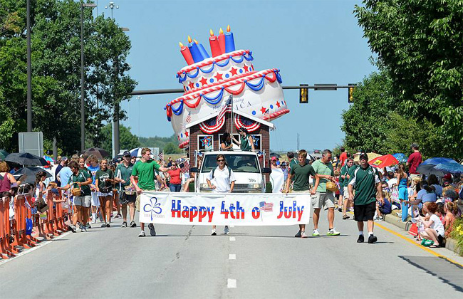 """young men holding """"Happy 4th of July"""" sign in front of large American flag-colored cake during a parade"""