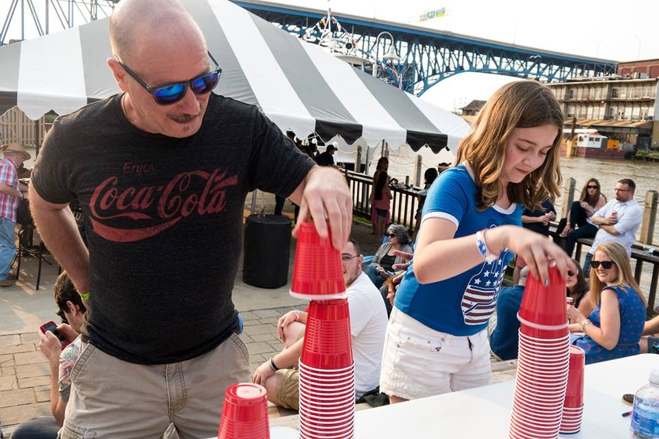 man and young girl stacking red plastic cups in front of tent